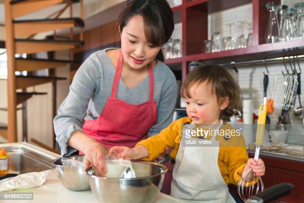 Young girl helping her mother in the kitchen