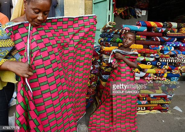 A young girl helps her mother fold pieces of fabric at a market in Abidjan on March 18 2014 AFP PHOTO / ISSOUF SANOGO