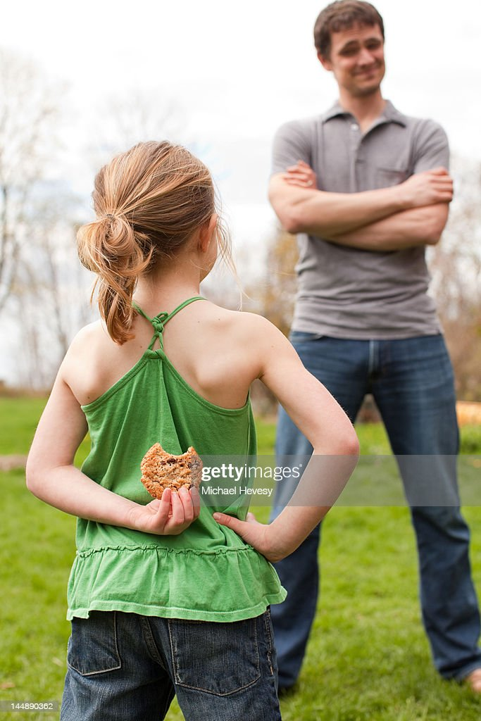 A young girl hiding a cookie from her father : Foto stock
