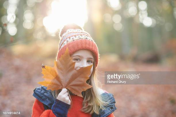 Young girl hiding behind a leaf in Autumnal woodland