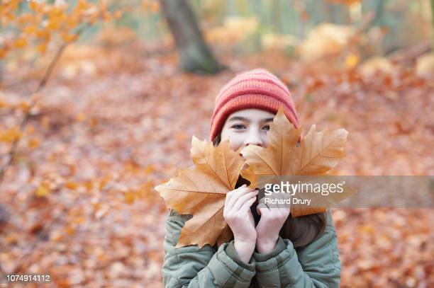 Young girl hiding behind leaves in Autumnal woodland