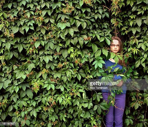 Young girl hiding in a bush