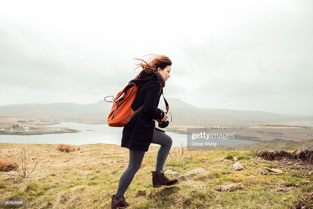 A young girl hiking alone in the wind : Stock Photo