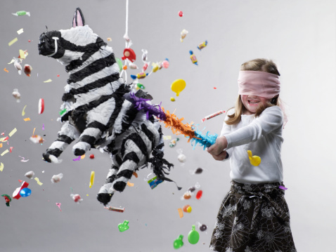 Young girl hitting pinata, candy flying - gettyimageskorea