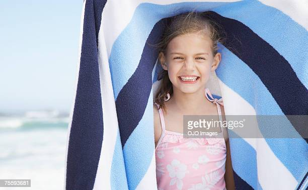 A young girl holding a beach towel