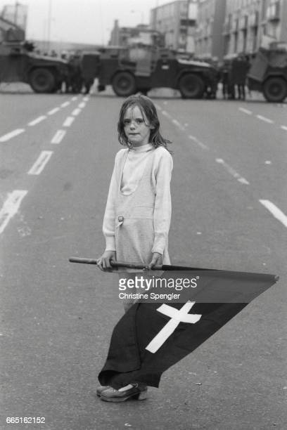 Young girl, holding a black flag marked with a white cross, stands as a symbol of Catholicism in Northern Ireland as she waits in an empty street,...
