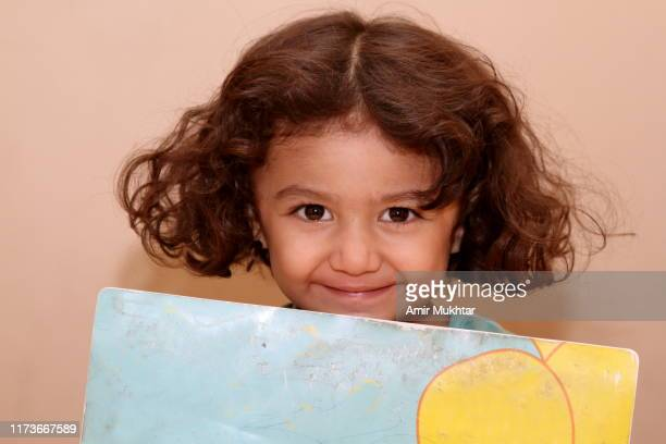 a young girl holding a coloring book and looking at camera - punjab pakistan stock pictures, royalty-free photos & images