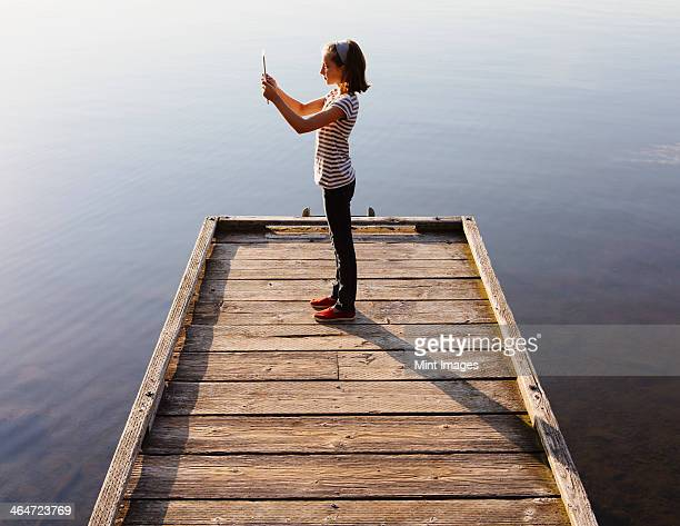 A young girl holding a digital tablet in front of her,standing on a wooden dock over the water.