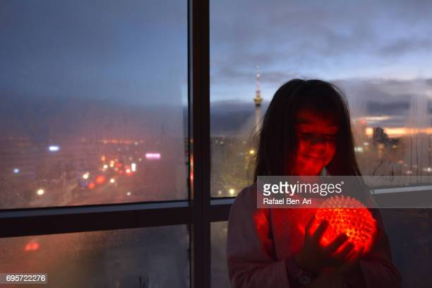 young girl holding a glowing red ball - rafael ben ari stockfoto's en -beelden