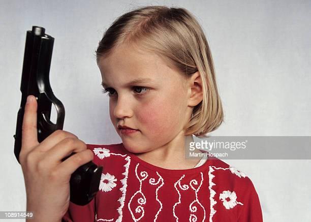 A young girl holding a gun