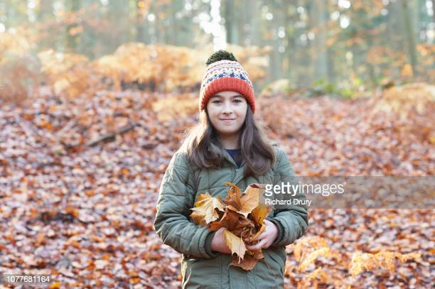 Young girl holding a handfuls of leaves in autumnal woodland