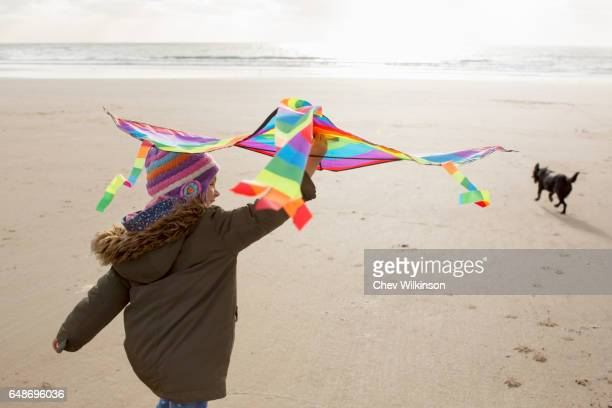 Young Girl holding a kite running on a beach with a dog