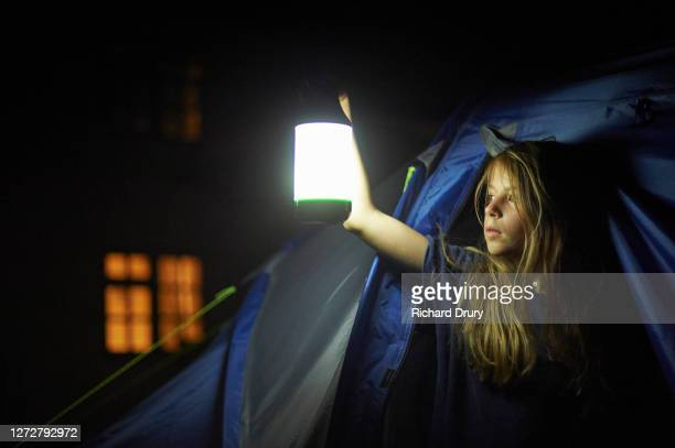 a young girl holding a lantern and looking out of her tent - richard drury stock pictures, royalty-free photos & images
