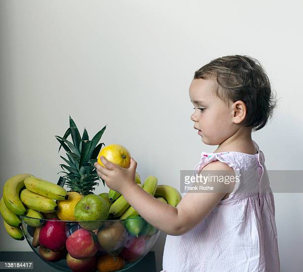 young girl holding a lemon in here hand
