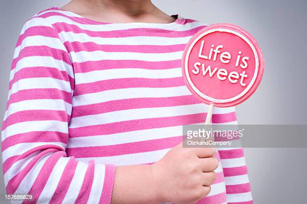 Young Girl Holding A Lollipop Saying Life Is Sweet