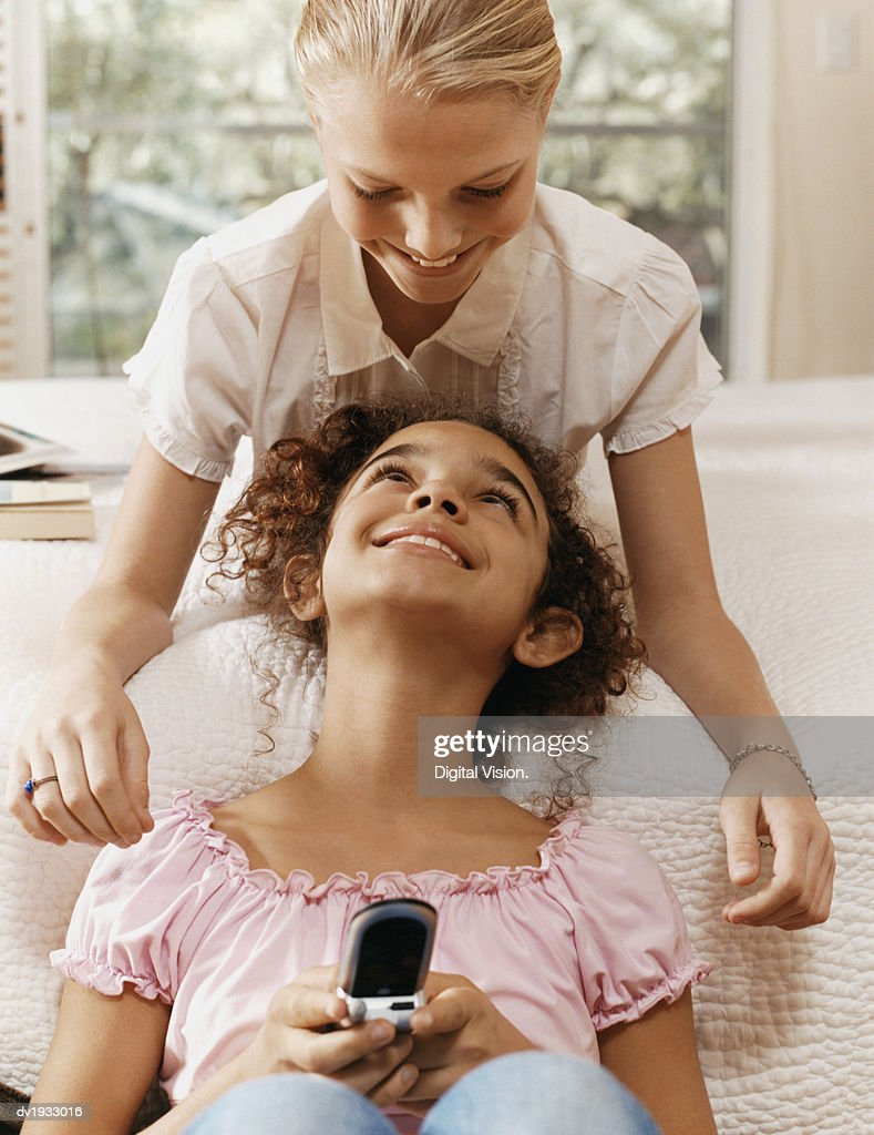 Young Girl Holding a Mobile Phone Face to Face With Another Girl in a Bedroom : Stock Photo