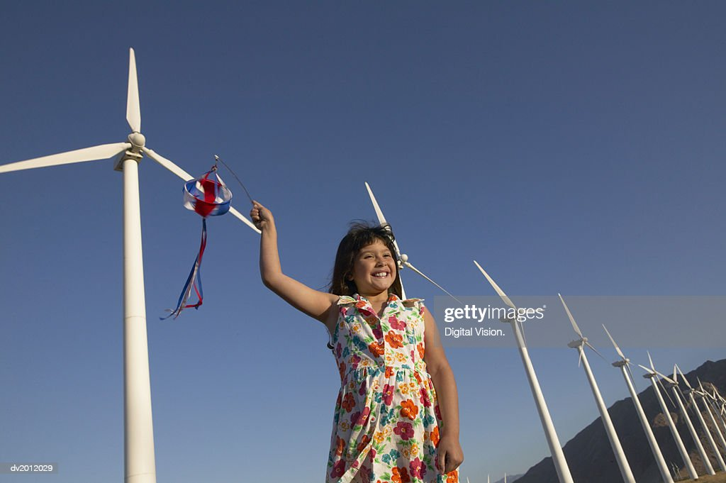 Young Girl Holding a Pinwheel Standing in a Wind Farm : Stock Photo