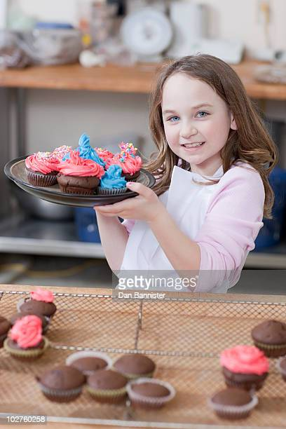 Young girl holding a plate of cupcakes