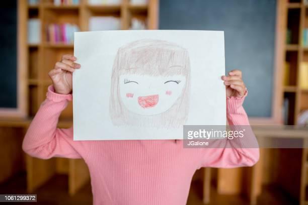 彼女の顔の前に描かれた自画像をもつ少女 - 絵画 ストックフォトと画像