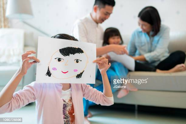 Young girl holding a self drawn portrait in front of her face