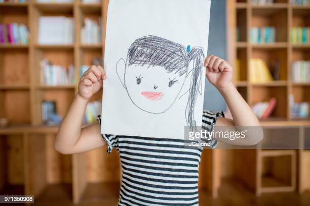 young girl holding a self drawn portrait in front of her face - self portrait stock pictures, royalty-free photos & images