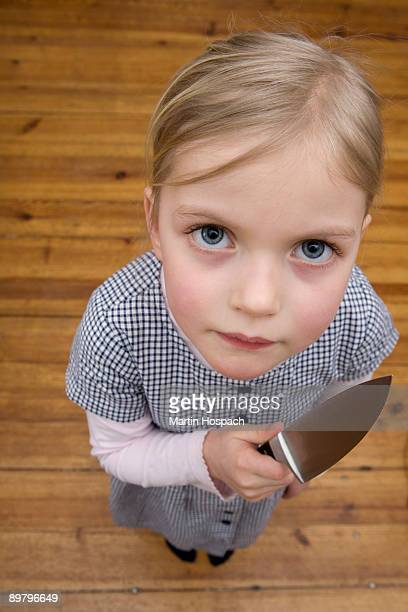 A young girl holding a sharp knife menacingly