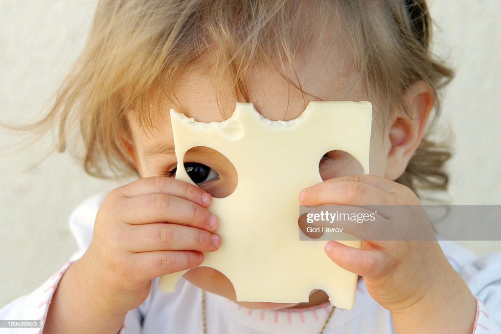 Young girl holding a slice of cheese over her face : Stock Photo