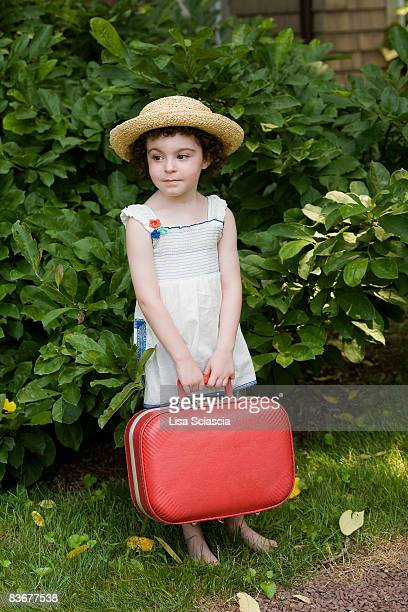 A young girl holding a suitcase waiting