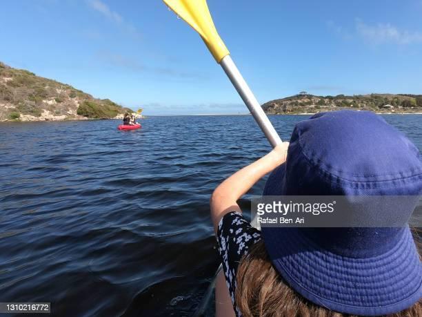 young girl  holding an oar kayaking over a river - rafael ben ari - fotografias e filmes do acervo