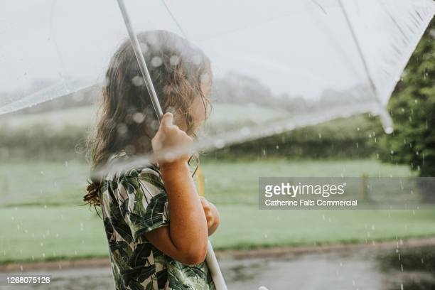 young girl holding an umbrella in the rain - smart stock pictures, royalty-free photos & images