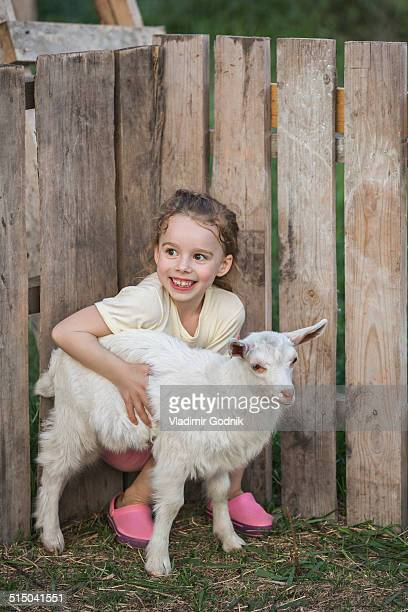 Young girl holding baby goat in park