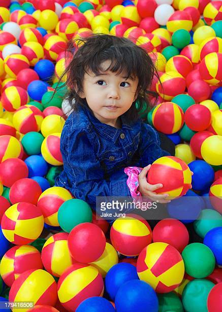 Young girl holding ball in colorful ball pit