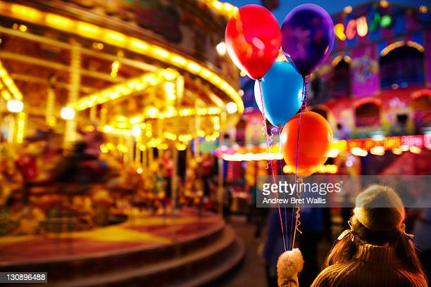 Young girl holding balloons at the fairground