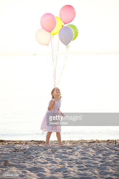 Young girl holding balloons on a beach at sunset