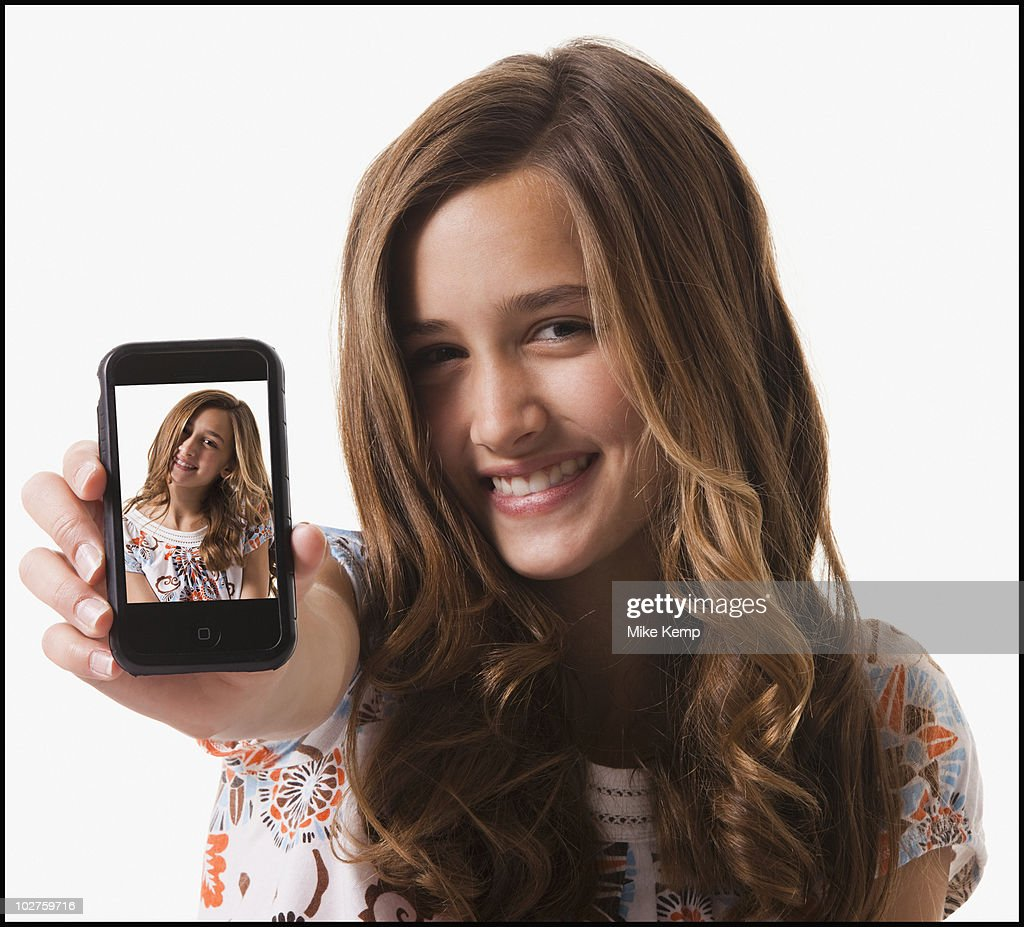 Young girl holding cellular phone : Stock Photo