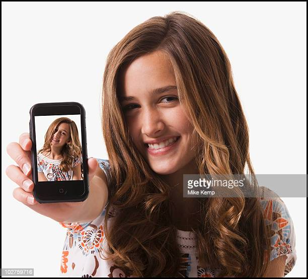 young girl holding cellular phone - photo messaging stock photos and pictures