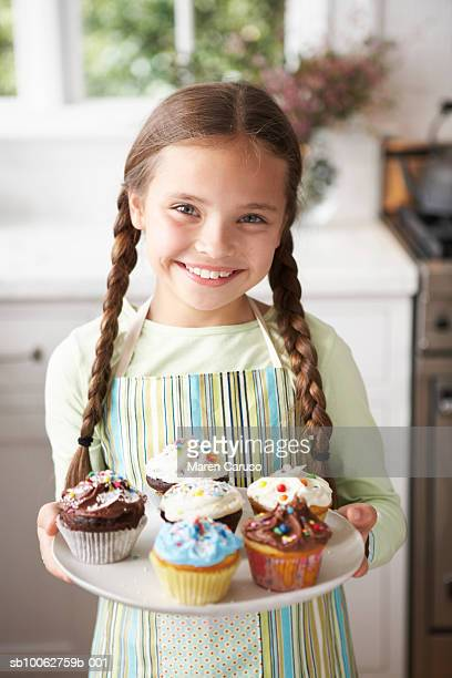Young girl (8-9) holding cupcakes. Looking at camera, smiling