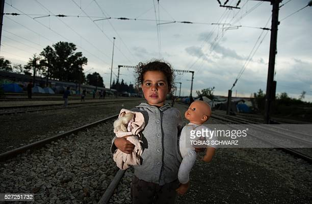 A young girl holding dolls poses on the railroad tracks near a makeshift camp for migrants and refugees near the village of Idomeni not far from the...