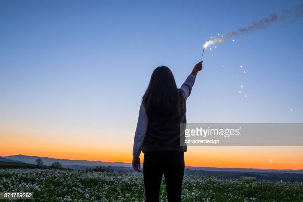 Young girl holding fireworks outdoors