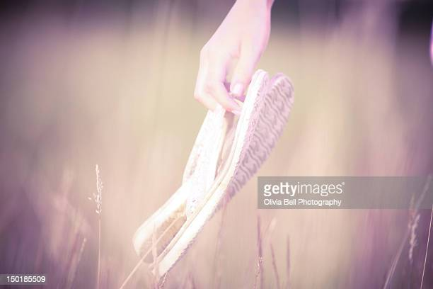 Young girl holding flip flops in her hand