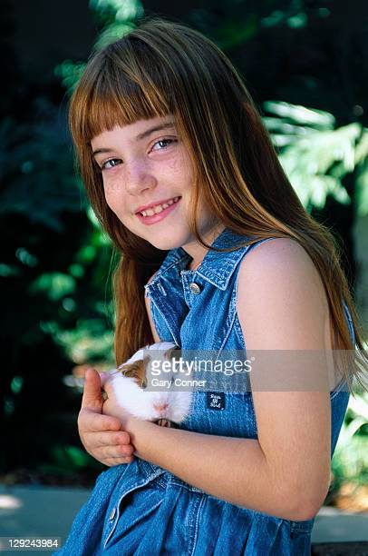 Young girl holding guinea pig, Los Angeles, CA