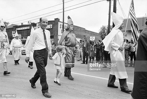 A young girl holding hands with robed Ku Klux Klansmen walks in a parade to support the Vietnam War An African American protester at the parades...
