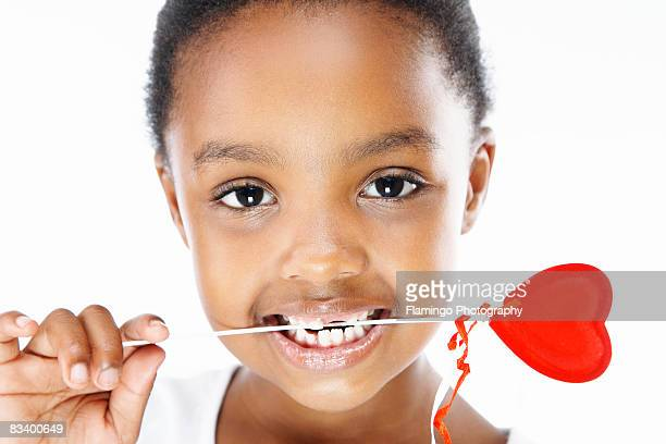 young girl holding heart lollipop in her teeth - flamingo heart stock pictures, royalty-free photos & images