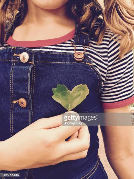 Young girl holding heart shaped leaf to her chest