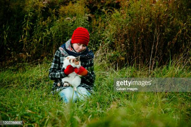 young girl holding her cat outdoors on a cold october day - cat with red hat stock pictures, royalty-free photos & images