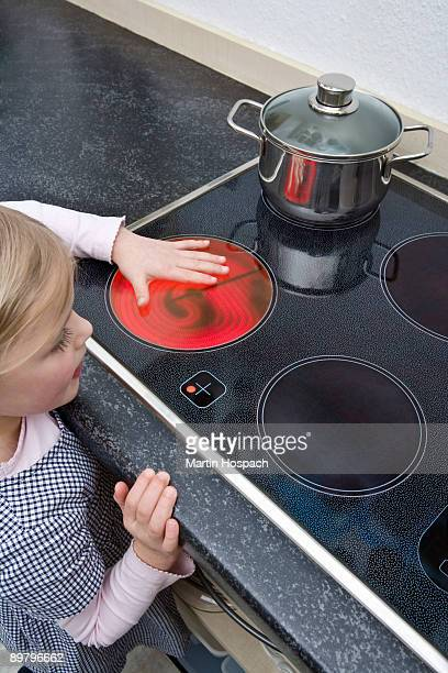 A young girl holding her hand over a hot electric stove burner