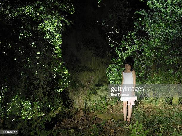 A young girl holding her teddy bear in a woodland at night
