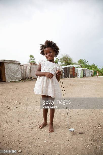 young girl holding homemade toy in front of tents - haiti stock-fotos und bilder