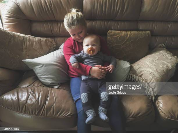 Young girl holding infant while sitting on a sofa