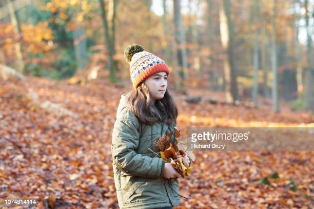 Young girl holding leaves in Autumnal woodland